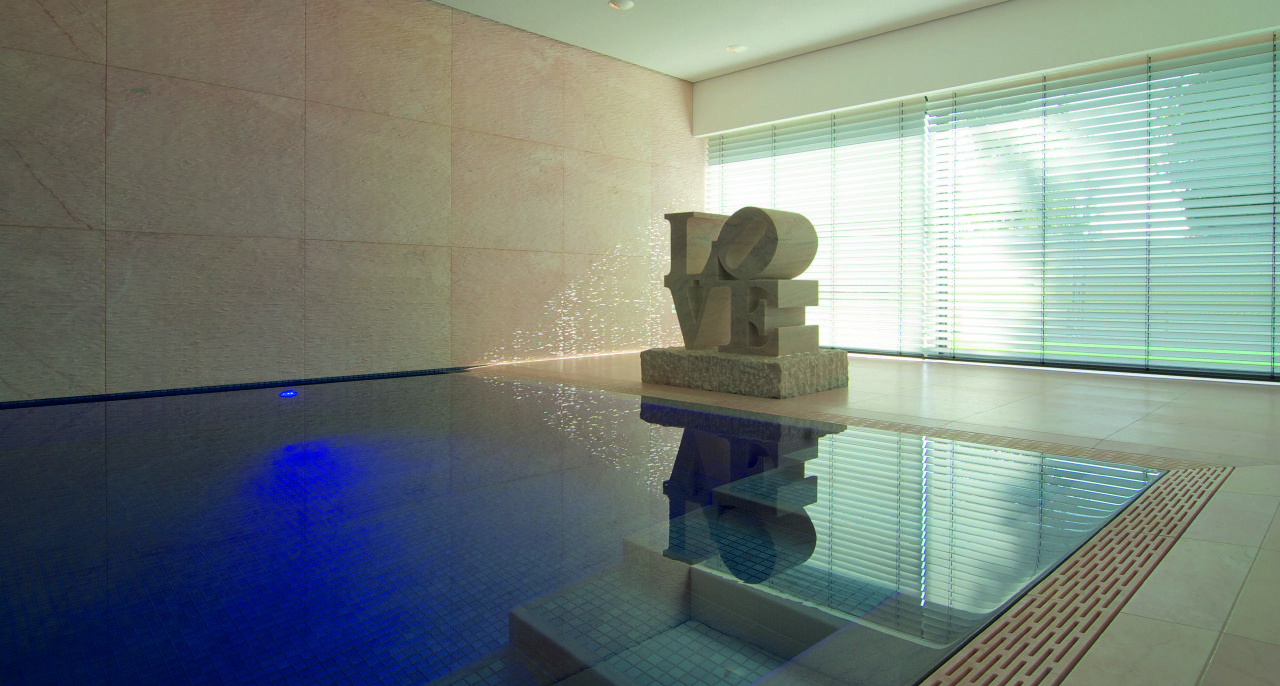 Pool mit Mosaik und Naturstein und Tendenza Wand